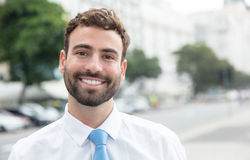 Laughing businessman with beard and blue tie in the city Stock Photography