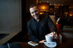 Laughing businessman drinking coffee in restaurant Stock Photos