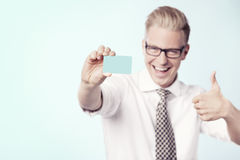 Laughing businessman giving thumbs up at blank card. Royalty Free Stock Photography