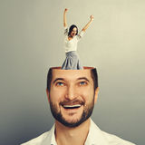 Laughing businessman and happy woman. Laughing young businessman with open head. young excited businesswoman dancing and raising hands up in the man's head Royalty Free Stock Images
