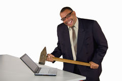 Laughing businessman hitting laptop. A laughing mature African-American businessman hitting his laptop with a sledgehammer, isolated on white background Royalty Free Stock Image