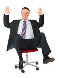 Laughing businessman on office chair Stock Photos