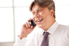 Laughing businessman on the phone in his office Stock Image