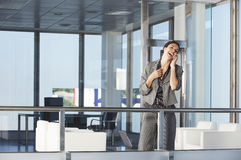 Laughing Businesswoman On Call In Office Corridor Stock Image