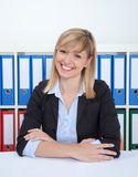 Laughing businesswoman with dark eyes and blonde hair at office Royalty Free Stock Image