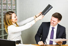 Laughing businesswoman is hitting the businessman royalty free stock photos