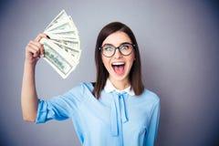 Laughing businesswoman holding bills of dollar Royalty Free Stock Image