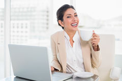 Laughing businesswoman holding cup while working on laptop Stock Photography