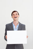 Laughing businesswoman holding white card Stock Photography