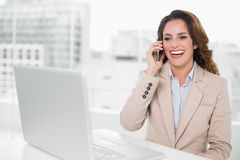 Laughing businesswoman on the phone at her desk Stock Photo