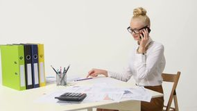 Laughing businesswoman on the phone at her desk in stock footage