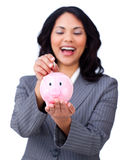 Laughing businesswoman saving money in a piggybank Stock Images