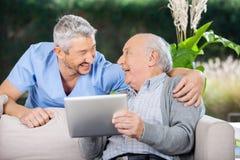 Laughing Caretaker And Senior Man Using Tablet. Laughing male caretaker and senior men using tablet computer at nursing home porch stock image
