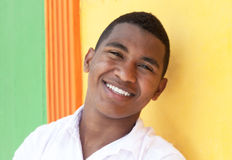 Laughing caribbean guy in front of a colorful wall Stock Photo