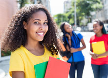 Laughing caribbean student in the city with friends Royalty Free Stock Photo