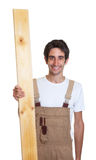 Laughing carpenter with wooden beam Royalty Free Stock Photos