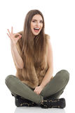 Laughing Casual Sitting Girl Showing Ok Hand Sign. Beautiful young woman in brown fur waistcoat and khaki pants sitting on floor with legs crossed, laughing and Stock Photography