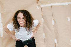 Cheerful woman on craft paper background. Laughing casual woman with curls holding hands on waist and bending forward looking at camera against craft paper Royalty Free Stock Photography