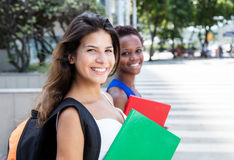 Laughing caucasian female student with african american girlfrie Stock Photo
