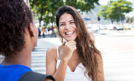 Laughing caucasian girl speaking with african american girlfriend Stock Image