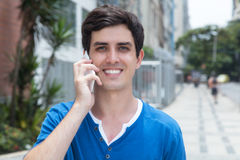Laughing caucasian guy in blue shirt with phone in the city. With modern buildings in the background Royalty Free Stock Photos