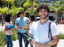 Laughing caucasian male student with group of students. Outdoor on campus of university in summer Royalty Free Stock Photos