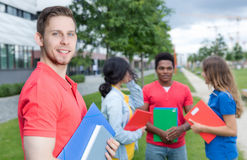 Laughing caucasian male student with stubble and multiethnic friends Stock Images