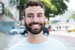 Laughing caucasian man with beard outdoor in city. With streets and buildings in the background Royalty Free Stock Photo