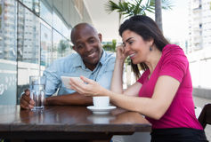 Laughing caucasian woman and african american man looking at mob Stock Images