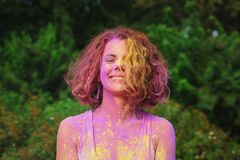 Laughing caucasian model in white t shirt posing covered by colo. Laughing caucasian woman in white t shirt posing covered by colorful dry paint Holi stock image