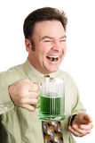 Laughing and Celebrating St Patricks Day. Irish American man celebrating St. Patrick's Day with a green beer and laughing.  Isolated on white Royalty Free Stock Image