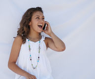 Laughing on cell phone. A teen girl is laughing while talking on her cell phone stock images
