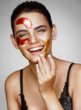 Laughing charming woman with color patches on her face Royalty Free Stock Image