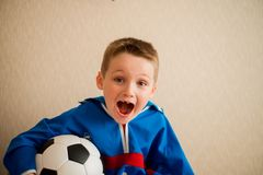 Laughing cheerful boy with a football in a blue sport uniform. The fan sits on a wooden chair watching football on TV.  Royalty Free Stock Photos