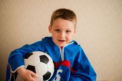 Laughing cheerful boy with a football in a blue sport uniform. The fan sits on a wooden chair watching football on TV.  Stock Image
