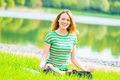 Laughing cheerful girl in lotus position Stock Images