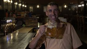 Laughing cheerful man having a beer and watching TV at the bar -. Laughing cheerful man having a beer and watching TV at the bar stock video