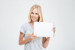 Laughing cheerful pretty girl showing blank notebook Stock Image