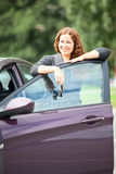 Laughing cheerful woman standing near new car Royalty Free Stock Photo