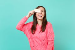 Laughing cheerful young woman in knitted pink sweater covering eye with credit card in hand isolated on blue turquoise. Wall background, studio portrait. People stock photography