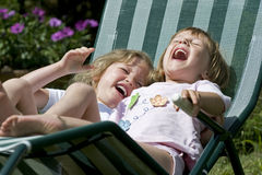Laughing chicks. Two little girls having fun on a rocking chair Stock Images