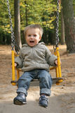 Laughing child. Small blonde boy playing on the swing. 2 years old boy is smiling and looking at camera. Autumn season Royalty Free Stock Image