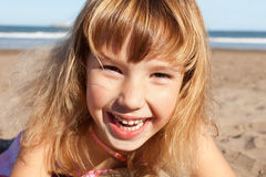 Laughing child. Portrait of a laughing little girl at the beach stock image