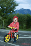 Laughing Child. Child is sitting on a bycicle with trees and mountains in background Stock Image