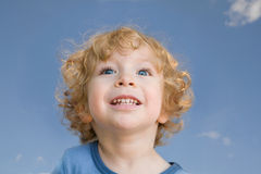 Laughing child against blue sky close-up Royalty Free Stock Image