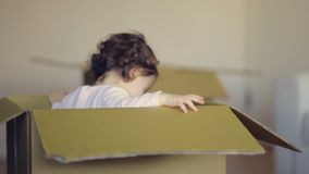 Laughing child girl sitting in cardboard boxe in her new home stock video