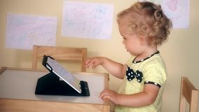 Laughing child girl touch tablet computer screen sitting near table stock video