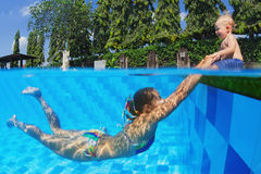Laughing child with joyful mother swimming in the pool. Joyful little baby having a fun and laughing with diving mother in swimming pool with blue water during Royalty Free Stock Photography