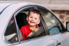 A laughing child looks out of an open car window stock image