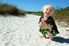 Laughing Child Playing in Sand at Beach Stock Photography
